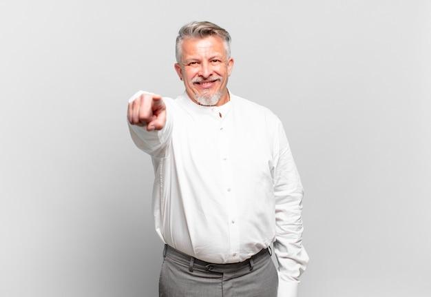 Senior zakenman wijzend op camera met een tevreden, zelfverzekerde, vriendelijke glimlach, jou kiezen