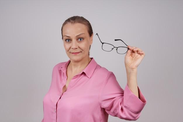 Senior zakenvrouw in een roze blouse stijgt haar bril op. foto op een grijze achtergrond met kopie ruimte.