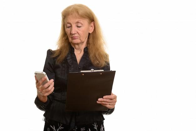 Senior zakenvrouw klembord houden tijdens het gebruik van haar telefoon