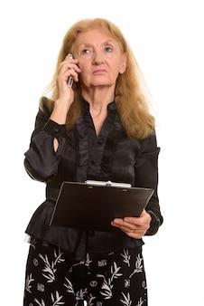 Senior zakenvrouw klembord houden tijdens het praten
