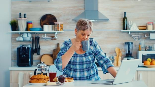 Senior zakenvrouw koffie drinken en werken op laptop in de keuken tijdens het ontbijt. oudere gepensioneerde die vanuit huis werkt, telewerken met behulp van externe internetbaan online communicatie op modern