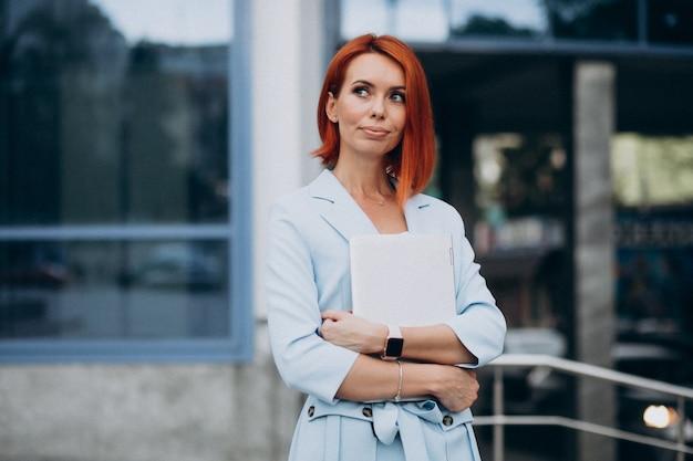 Senior zakenvrouw met laptop door office center