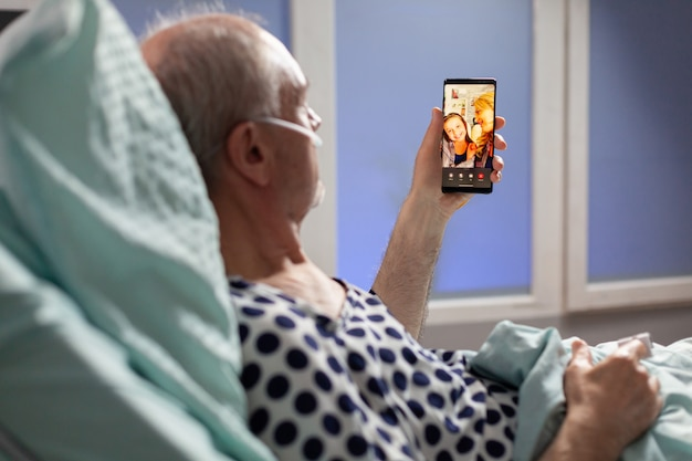 Senior zieke man ademt door zuurstofslang en zegt hallo