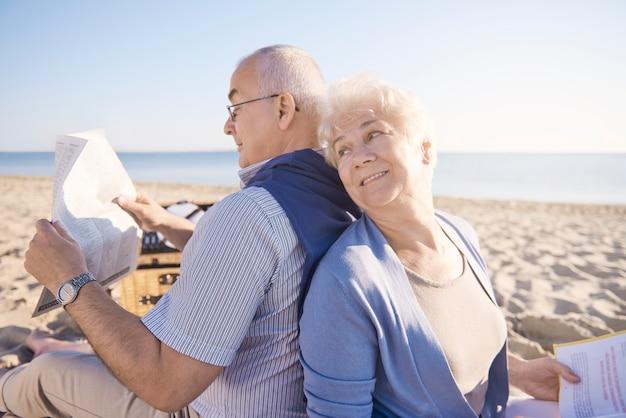 Senioren die op het strand lezen