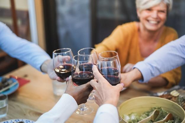 Senioren die plezier hebben met juichen met wijn tijdens het diner op het terras - focus op vrouwelijk gezicht