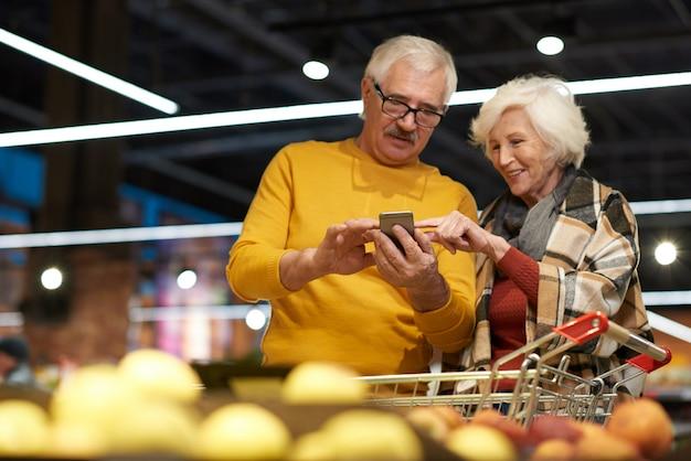 Senioren die smartphone in supermarkt gebruiken