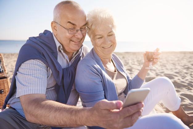 Senioren die wijn drinken en naar hun mobiele telefoon kijken