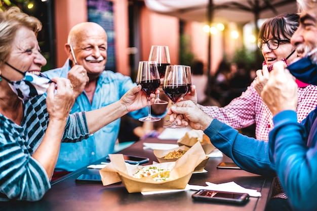 Senioren die wijn roosteren in de restaurantbar met open gezichtsmaskers