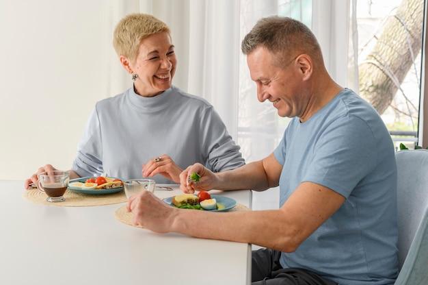 Senioren echtpaar familie ontbijten thuis, eten gezond voedsel, glimlachen en loven zittend aan
