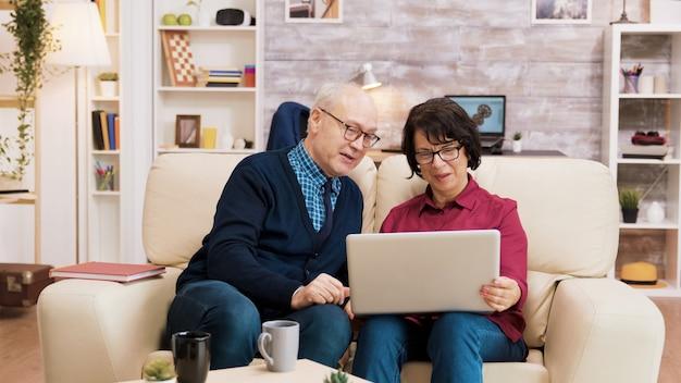 Senioren koppel tijdens een videogesprek zittend op de bank in de woonkamer. oudere mensen die moderne technologie gebruiken