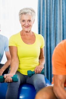 Senioren met behulp van oefening bal en gewichten