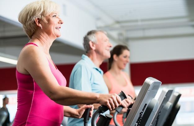 Senioren trainen op crosstrainer met personal trainer aan de g