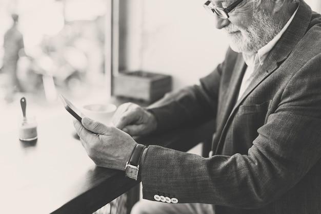 Senoir blanke man met mobiele telefoon in café