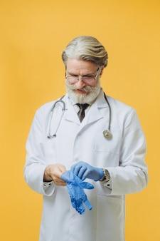 Senor arts witte jas en stethoscoop dragen, geïsoleerd op gele muur, draagt blauwe handschoenen