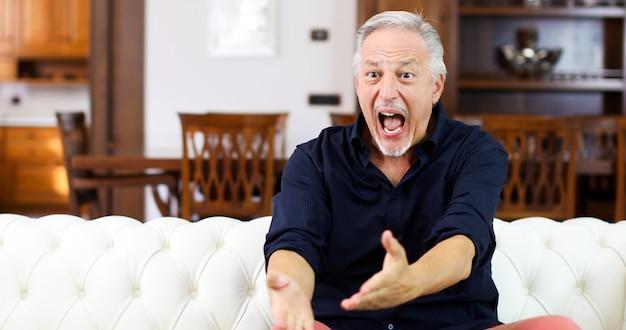 Senor kerel kijkt sport op tv en schreeuwt