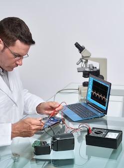 Senor mannelijk tech fixeert moederbord in reparatiewerkplaats voor elektronische apparatuur