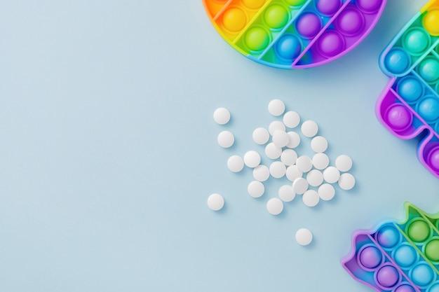 Sensorisch speelgoed poppit en pillen op blauwe achtergrond als medicijn voor adhd of autisme