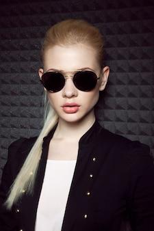 Sensueel blond vrouwelijk model met make-up en paardenstaartkapsel met zwarte zonnebril