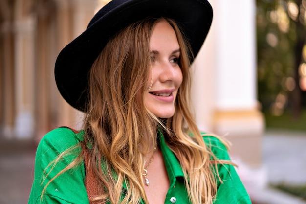 Sensueel close-up portret van stijlvolle blonde vrouw met krullende haren, natuurlijke make-up en mooi gezicht, met zwarte hoed