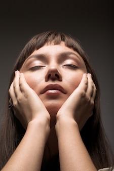Sensueel donker portret van een jonge vrouw met gesloten ogen