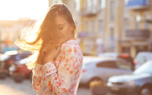 Sensueel donkerbruin meisje die blouse en roze jasje dragen die bij de achtergrond van de avondstad stellen. ruimte voor tekst
