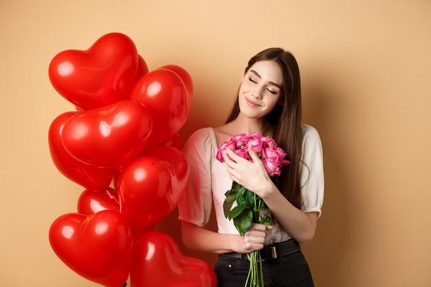 Sensueel en romantisch meisje knuffelen boeket roze rozen
