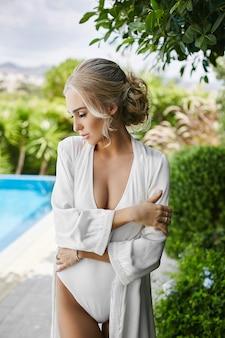 Sensueel en sexy blonde model vrouw met perfect lichaam in zwembroek en peignoir, staat met gesloten ogen en poseren bij het zwembad in de open lucht