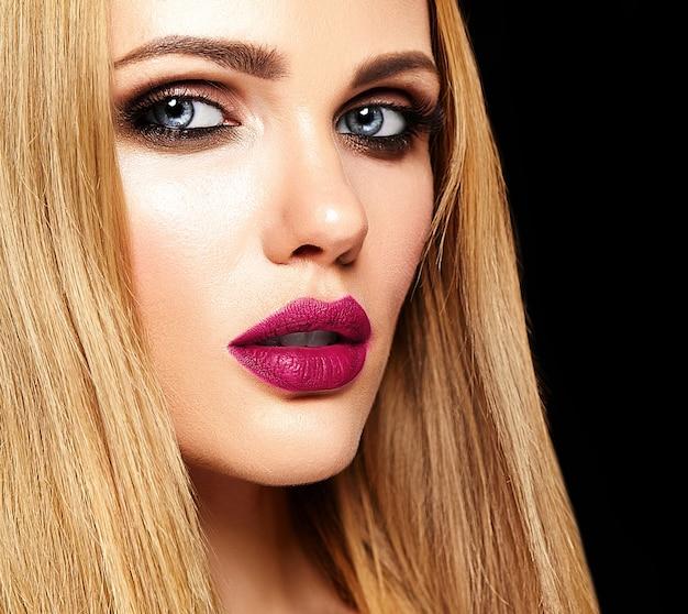 Sensueel glamourportret van mooi vrouwenmodel met verse dagelijkse make-up met roze lippenkleur en schoon gezond huidgezicht op de achtergrond van studiolichten