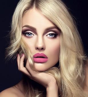 Sensueel glamourportret van mooie blonde vrouwmodel dame met lichte make-up en rode lippen wat betreft haar gezicht, met gezond krullend haar op zwarte achtergrond