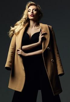 Sensueel glamourportret van mooie blonde vrouwmodel dame met verse make-up in klassiek zwart kostuum en overjas