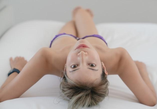 Sensueel jong vrouwenportret dat op haar bed legt.