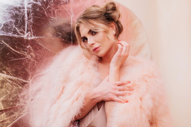 Sensueel krullend meisje in trendy roze bontjas kijkt koket en raakt haar hand aan. portret van schattige blonde jonge vrouw in pluizige kleding die graag op zilveren glitter achtergrond poseren