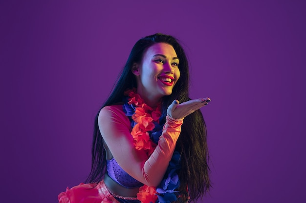 Sensueel, kussend. hawaiiaans brunette model op paarse muur in neonlicht. mooie vrouwen in traditionele kleding glimlachen en plezier hebben. heldere feestdagen, feestkleuren, festival.