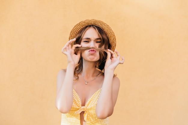 Sensueel meisje in zomerkleding die speels op goede dag stellen. positieve stijlvolle vrouw geïsoleerd.