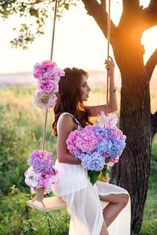 Sensueel mooi meisje met perfecte glimlach in een witte jurk zittend op een houten schommel met een boeket van tedere gekleurde bloemen.