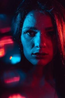 Sensueel portret van een mooi aantrekkelijk meisje dat door het glas met regendruppels kijkt