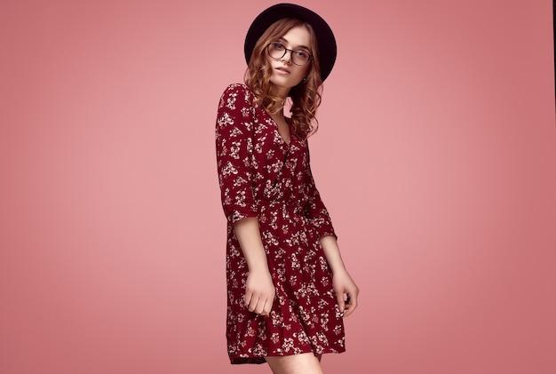 Sensueel portret van elegante glamour hipster meisje in rode mode jurk, zwarte hoed en bril poseren op kleurrijke roze achtergrond in studio