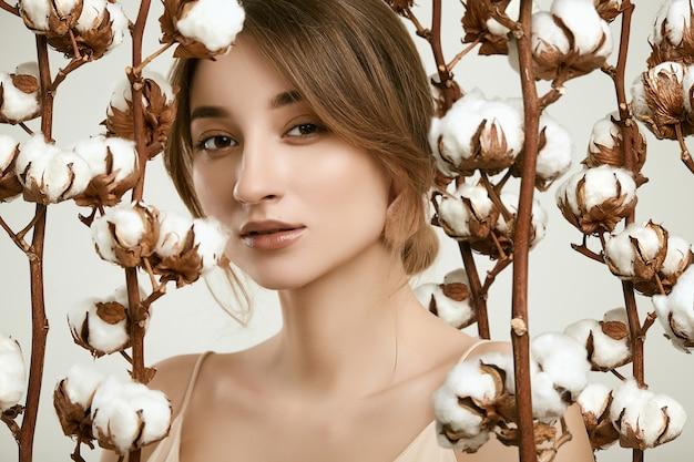 Sensueel portret van glamour vrouw model onder katoenen twijgen