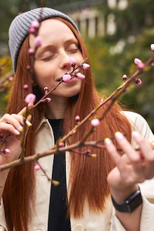 Sensueel portret van mooie roodharige vrouw in hoed ruikende roze bloemen in het voorjaar stijlvolle rustige vrouw poseren in bloeiende boom met bloemen in voorjaar park kopie ruimte close-up