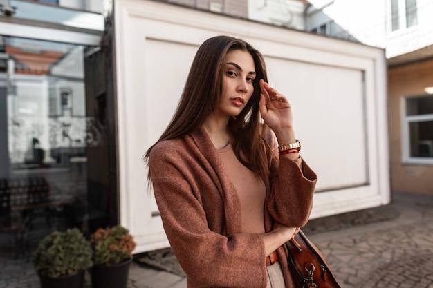 Sensueel portret vrij elegante schattige jonge vrouw met sexy lippen met bruin lang haar in modieuze lentejas buiten in de stad. mooi schattig meisje mannequin in stijlvolle kleding. elegante dame.