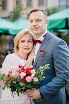 Sensueel romantisch ouder echtpaar met bloemboeket, naast elkaar buiten in de stad