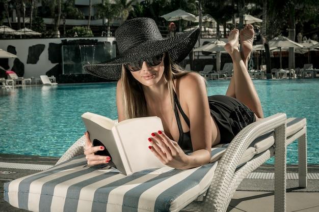 Sensueel vrouwelijk leesboek op ligstoel