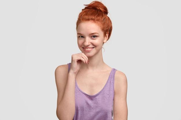 Sensueel vrouwelijk met rood haar, sproeten, houdt de hand onder de kin