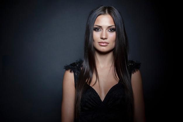 Sensueel vrouwelijk model met lang donkerbruin steil haar en lichte make-up, zwarte achtergrond