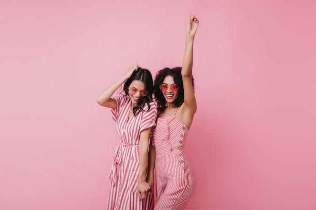 Sensuele afrikaanse dame die plezier heeft met haar beste vriend. indoor foto van schattige meisjes in roze kleren staan