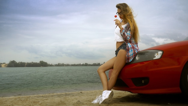 Sensuele blonde in glazen zit op een rode auto met lolly in haar handen aan de kust