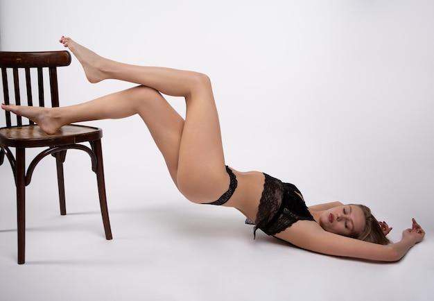 Sensuele blonde in sexy ondergoed ligt met haar benen gevouwen op een stoel