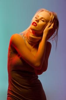 Sensuele blonde jonge vrouw met rode lippen staan