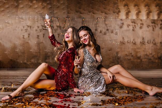 Sensuele blonde vrouw in fonkelingsjurk die champagne op de vloer drinkt