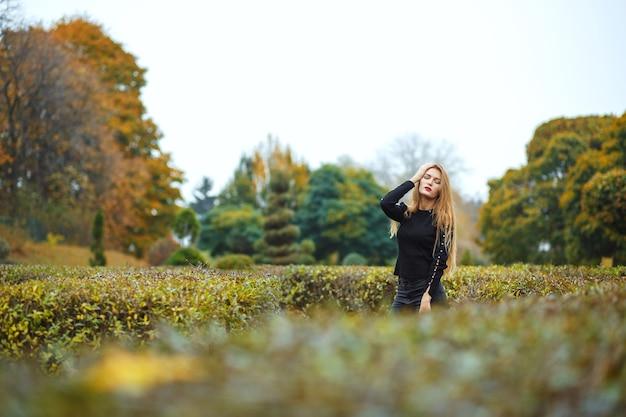 Sensuele blonde vrouw met rode lippen poseren in de herfsttuin. ruimte voor tekst
